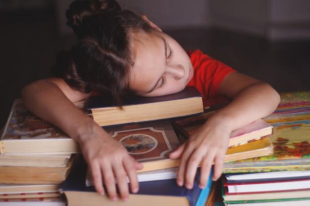 Sleeping girl with piles of books