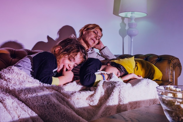 Sleeping kids with mother on couch