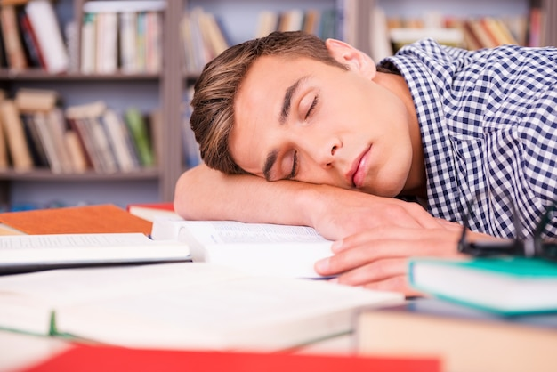 Sleeping in library. handsome young man sleeping while sitting in library and leaning his face at the desk