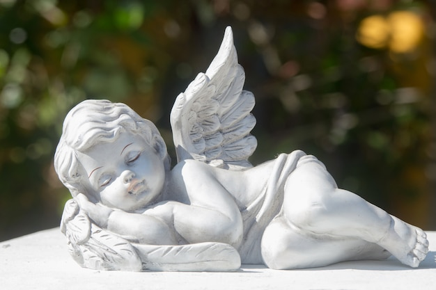 Sleeping of little cupid's ceramic doll on stone. items for house, garden, and interior