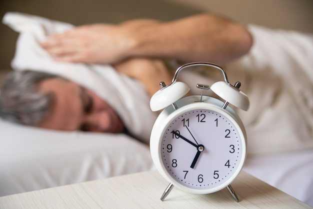 Sleeping man disturbed by alarm clock early morning.  sleepy you