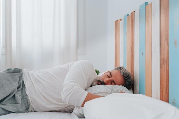 편안한 침대에서 잠옷을 입고 잠자는 50대 남성