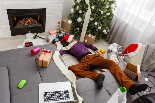 Спящий мужчина на диване после рождественской вечеринки.