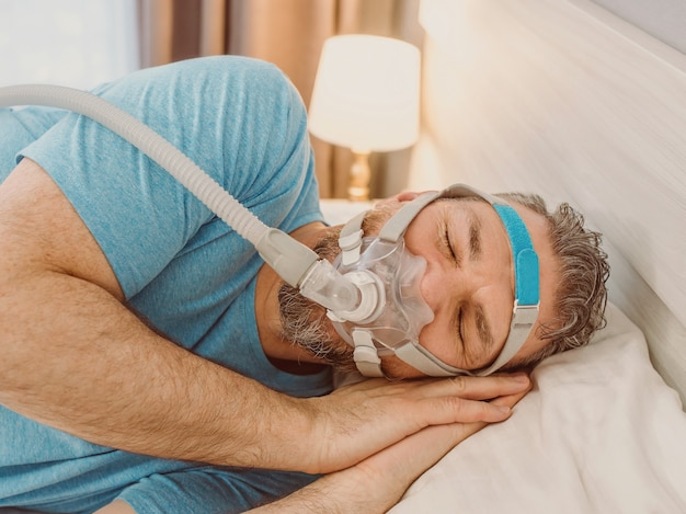 Sleeping man with chronic breathing issues using cpap machine in bed