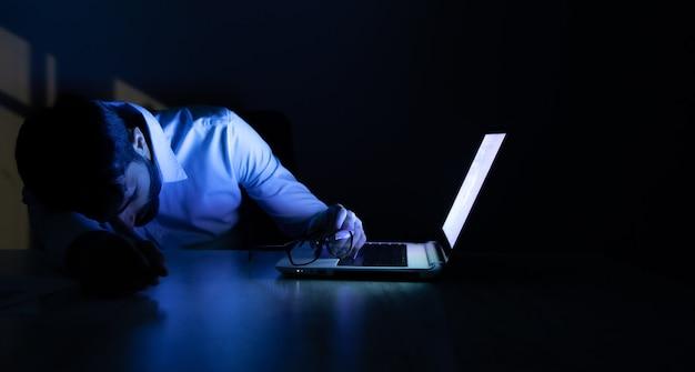 Спящий мужчина с компьютером на столе ночью