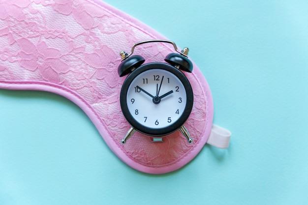 Sleeping mask and alarm clock on blue background