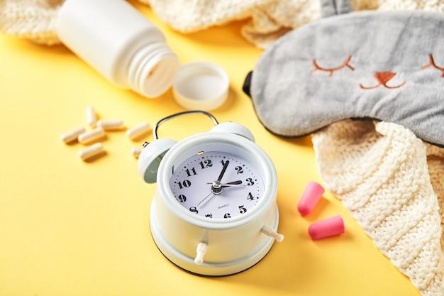 Маска для сна, будильник, беруши и таблетки. творческая концепция здорового ночного сна. спокойной ночи, гигиены сна, бессонницы