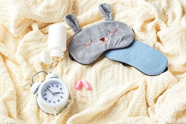 수면 마스크, 알람 시계, 귀마개 및 알약. 건강한 수면 창의적인 개념. 좋은 밤, 수면 위생, 불면증