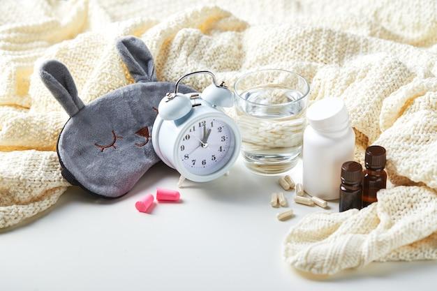 수면 마스크, 알람 시계, 귀마개, 에센셜 오일 및 알약. 건강한 수면 창의적인 개념. 좋은 밤, 수면 위생, 불면증