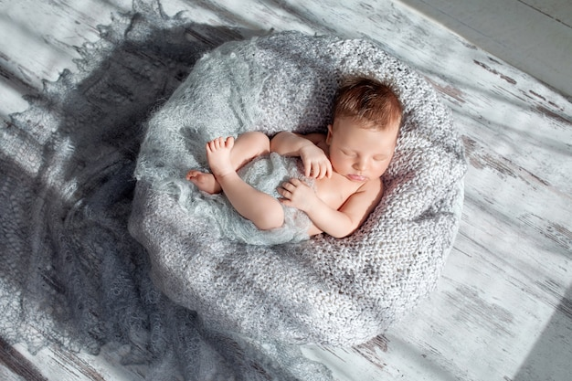 Sleeping newborn baby boy swaddled in a nest
