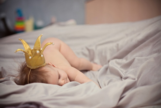 Sleeping newborn baby on the head with a baby crown
