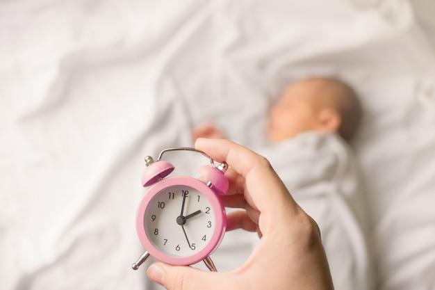Спящий новорожденный в пелену на белом одеяле