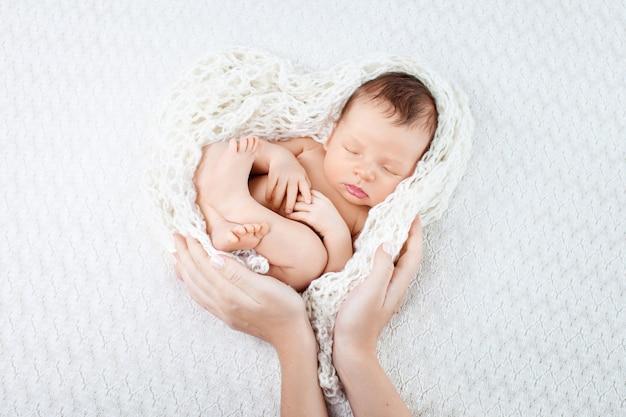 Спящий новорожденный в руках матери