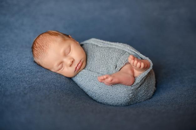 寝ている生まれたばかりの赤ちゃんはグレーブルーのニット生地に包まれています