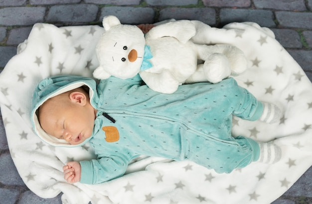 テディと毛布の上で眠っている新生児