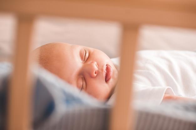 ベッドのクローズアップで横になっている眠っている新生児