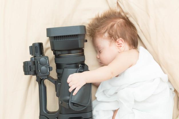 Sleeping newborn girl holding a video camera.