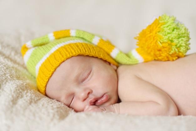 Спящий новорожденный носит забавную шляпу