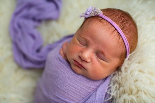 Спящая девятидневная новорожденная девочка, закутанная в фиолетовую пелену.