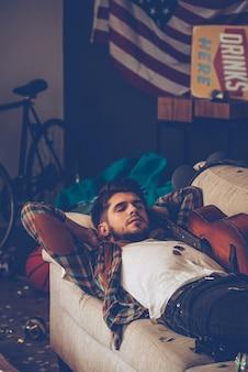 その二日酔いから眠ります。ソファに横になっている若いハンサムな男