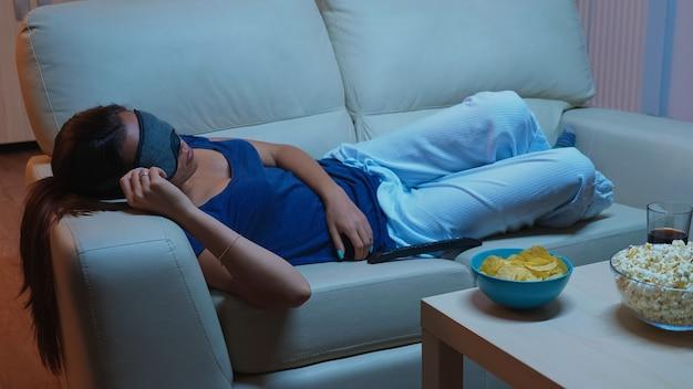 テレビの前で目を覆うマスクでソファで寝ています。映画の最中にソファで眠りに落ち、居間でテレビを見ながら目を閉じて、パジャマ姿で疲れ果てた孤独な眠そうな女性。