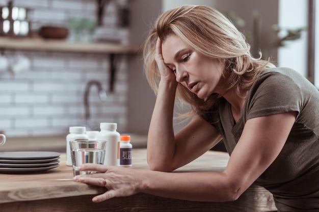 睡眠薬。落ち込んでいる金髪の女性が、自殺を考えて睡眠薬を飲みすぎている
