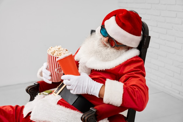 Sleeping saint nicholas in armchair with popcorn and cola