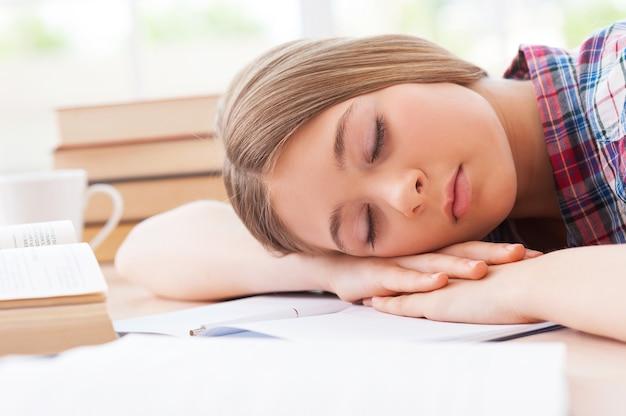 Спящая школьница. девочка-подросток спит, положив голову на школьную парту