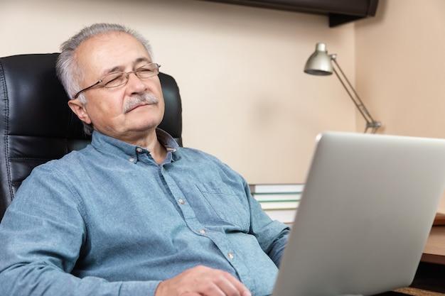 眠っているシニアビジネスマンは在宅勤務。眼鏡をかけた老人がラップトップを使用してリモートで作業しています。コロナウイルスコンセプト中のリモートワーク