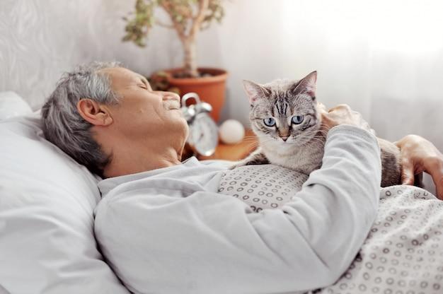 Спящий старший мужчина держит кота в руках