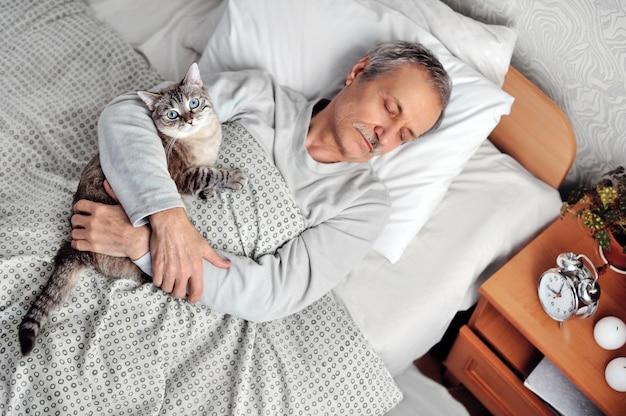 Спящий старший мужчина держит полосатый кот