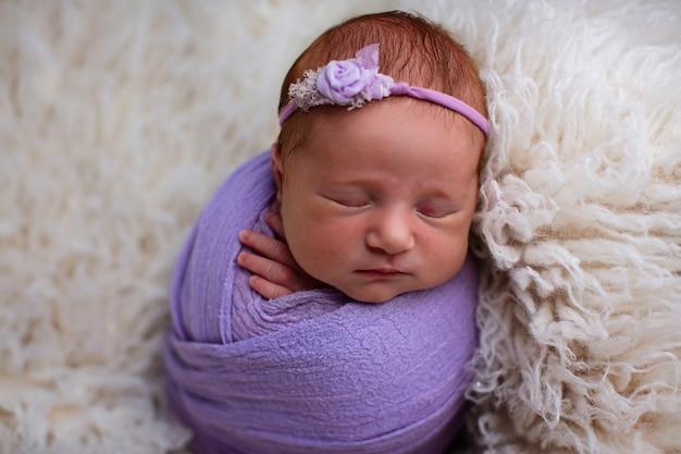 Спящая семидневная новорожденная девочка, закутанная в фиолетовую пелену.