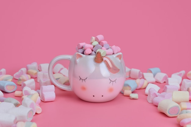 Sleeping unicorn cup on a pink background with mixed marshmallows and place for text. sweets concept with copy space.