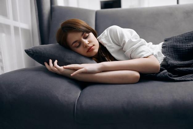 ソファの休憩所に横たわって自宅で眠っている女性。高品質の写真
