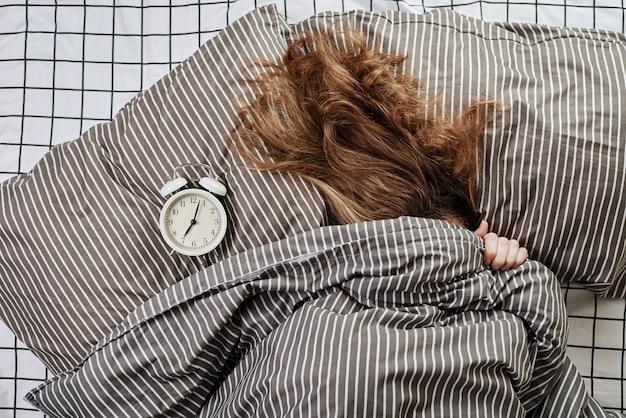 眠っている女性はベッドの毛布と枕のヴィンテージの目覚まし時計の下で覆われています。レイジーモーニングアナウェイクアップコンセプト