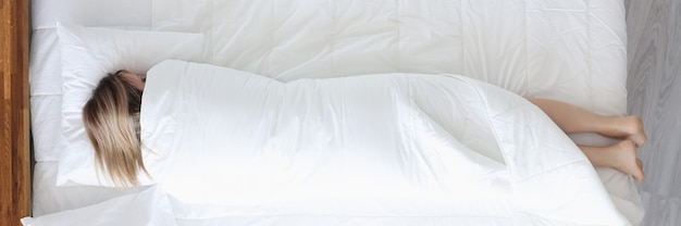잠자는 여자는 현대 사회 개념의 담요 외로움에 싸여 침대에 누워