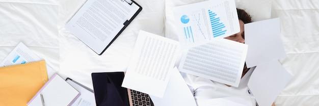 ノートパソコンと財務書類を持ってベッドで寝ている女性の不規則な労働時間と締め切り