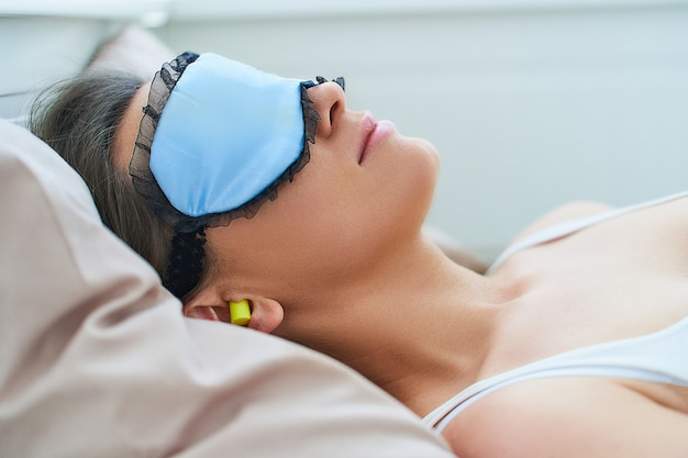 Спящая женщина использует маску для глаз и затычки для ушей для лучшего сна, защиты от шума и сладких снов