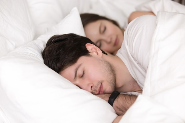 Sleeping young couple in bed, man wearing smart watch tracker