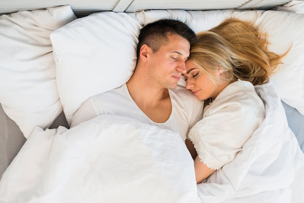 Sleeping young couple under blanket on bed