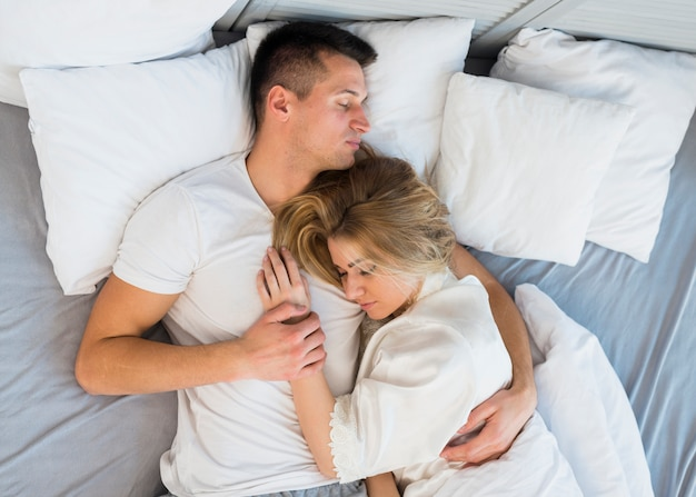Sleeping young couple hugging on bed