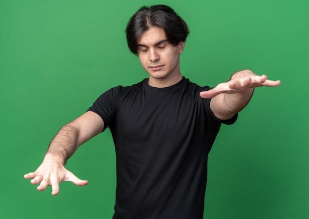 녹색 벽에 고립 된 카메라에 손을 잡고 검은 티셔츠를 입고 잠자는 젊은 잘 생긴 남자