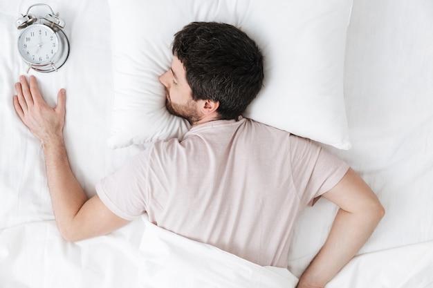 Спящий молодой человек утром под одеялом в постели лежит с будильником