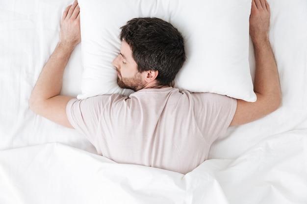 Спящий молодой человек утром под одеялом в постели лежит