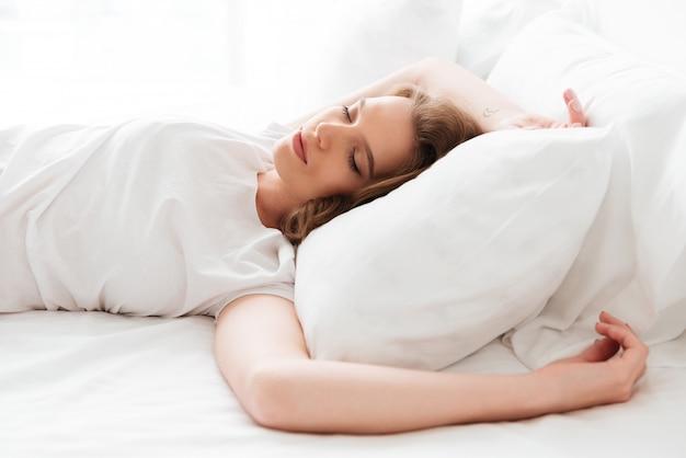 잠자는 젊은 여자는 눈을 감고 침대에 놓여 있습니다.