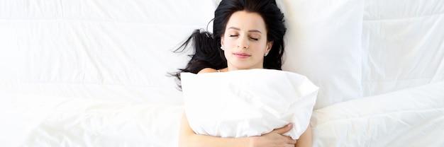 하얀 침대에서 잠자는 젊은 여성은 베개를 껴안고 편안하고 건강한 수면 개념을 가지고 있습니다