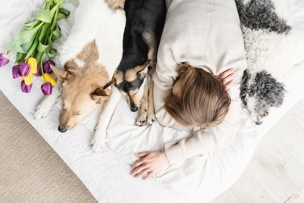 彼女の犬と一緒にベッドに横たわっているパジャマを着て眠っている若い女性