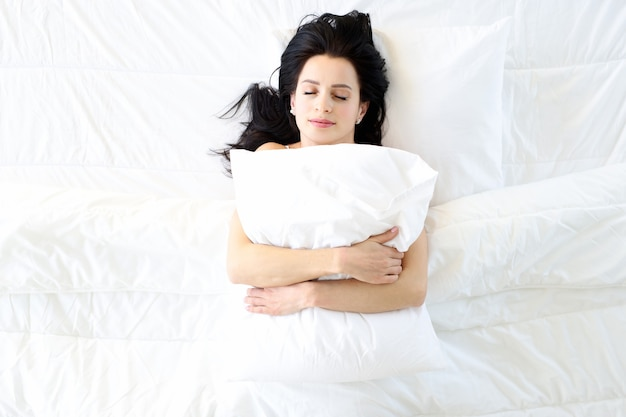 Sleeping young woman on white bed hugs pillow
