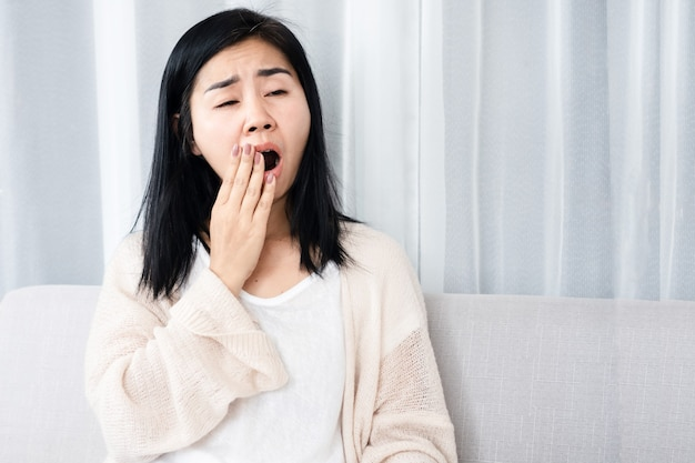 Sleepless asian woman yawning and tired from insomnia sitting on sofa