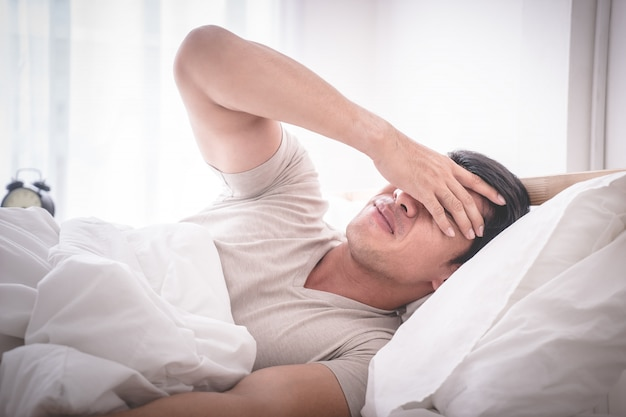 Sleepless hangover man on bed woke up with headache